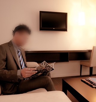 Gigolo David in a suit in hotel room